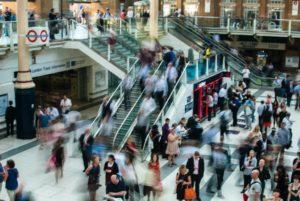 Menschenmassen bewegen sich in Hektik in einem Bahnhof.  Gelingendes Mood-Management wird zum zentralen Faktor.