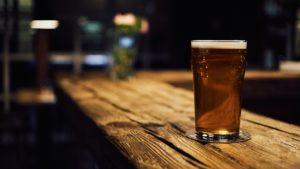 Alkohol während der Corona-Pandemie: Ein volles Bierglas wartet symbolisch auf einem Tresen darauf, getrunken zu werden.