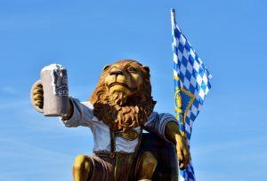 Auf dem Foto ist ein Löwe in Lederhosen zu sehen, der einen Bierkrug hochhält. Hinter ihm befindet sich die Bayrische Landesflagge.